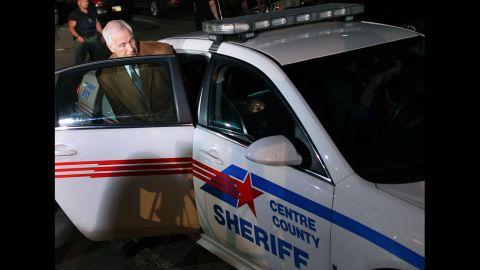 Sandusky is put into a police car.