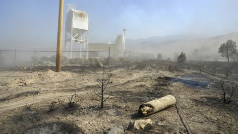 Smoldering earth and damage from the Dump Fire, which began June 21, can be seen outside a plant near Saratoga Springs, Utah, on Saturday, June 23.