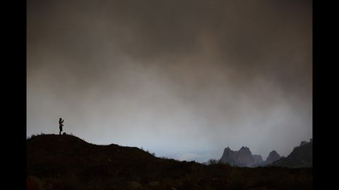 J'Amie Sirvaitis of Colorado Springs watches the Waldo Canyon Fire after winds pushed the fire into the Mountain Shadows neighborhood in Colorado Springs on Tuesday.