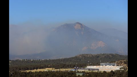 Hazy smoke from the Waldo Canyon Fire looms behind the Air Force Academy stadium on Wednesday, June 27, in Colorado Springs, Colorado. The fire expanded to 15,000 acres. More than 32,000 people have been evacuated.