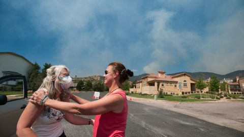 Jan Stone, right, comforts Angela Morgan as smoke from the Waldo Canyon Fire pours over the Mountain Shadows neighborhood of Colorado Springs on Tuesday.