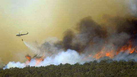 A helicopter drops water over the Wood Hollow Fire north of Fairview, Utah, on Tuesday, June 26
