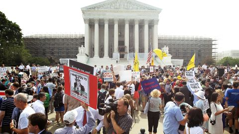 Journalists and supporters and protesters of the health care law gather outside the Supreme Court after the justices ruled in favor of its constitutionality in a narrow decision.