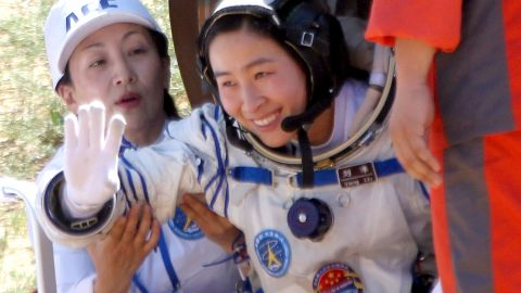 China's first female astronaut, 33-year-old Liu Yang waves as she emerges from the return capsule of the Shenzhou-9 spacecraft on June 29, 2012.<br />