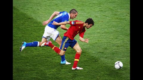 Cesc Fabregas of Spain runs with the ball past Leonardo Bonucci of Italy.