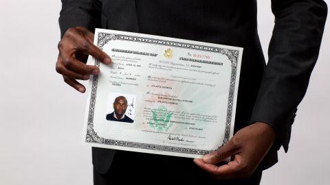 Stan Sowunmi of Nigeria displays his naturalization certificate after becoming a U.S. citizen.