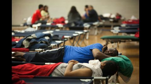 Tek Measho, center, and others rest on cots in a Red Cross shelter set up at Northwestern High School in Hyattsville, Maryland, after the heavy storms knocked out power to their apartment building.