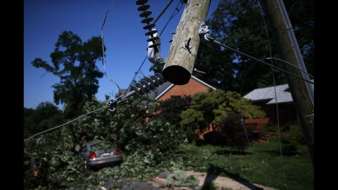 Power lines hang from a utility pole snapped in half and a fallen tree covers a car on Yorktown Boulevard in Arlington, Virginia.