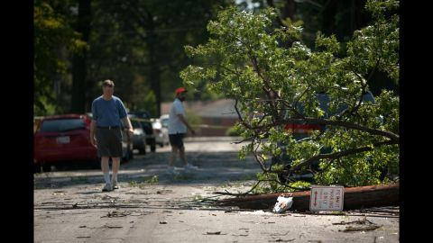 Neighbors inspect a downed tree on a heavily damaged block in Forest Glen, Maryland.