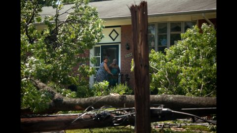 Resident Sandra Patterson, left, and friend Julia Gilliard inspect a downed tree in Patterson's front yard in Forest Glen, Maryland.