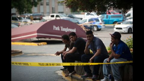 Residents sit in the parking lot of  the seven-story Park Tanglewood Apartments in Riverdale, Maryland, after heavy winds tore off much of the building's roof, forcing all of the residents to be evacuated from the building.