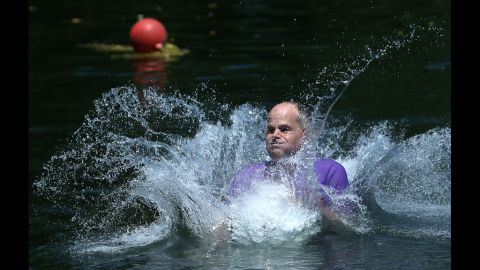 Gene Holmes splashes into a quarry lake after jumping from a rope swing on Monday, July 2, at the Beaver Dam Swimming Club in Cockeysville, Maryland.