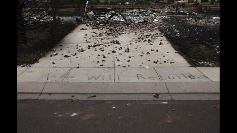 """The words """"We Will Rebuild"""" are seen written on the sidewalk in front of a house in Colorado Springs that was destroyed by the fire."""