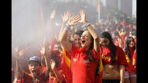 Supporters of Spain's national soccer team are hosed down before the team's victory parade in Madrid on Monday.