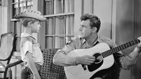"""Griffith plays the guitar for his television son, Opie, during """"The Runaway Kid."""""""