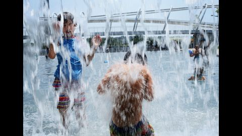 Ten-year-old Lilly Hwang-Geddes, left, of Ithaca, New York, plays in a fountain at the Yards Park on Thursday, July 5, in Washington.