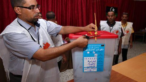 A Libyan election official opens a ballot box at a Tajura polling station.