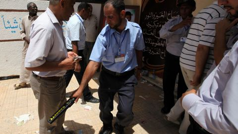 A voter goes through a security checkpoint outside a polling station in the Abu Slim neighbourhood of Tripoli.