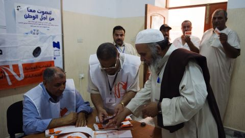 Libyan election workers check the identification card of a voter at a Tripoli polling station.