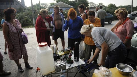 People gather to charge cell phones in Krymsk after flooding knocked out power to tens of thousands of residents.
