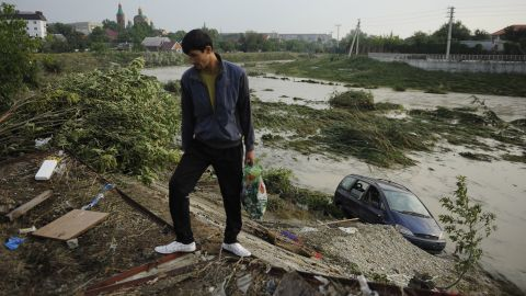 A man walks past an abandoned car Sunday in the town of Krymsk.