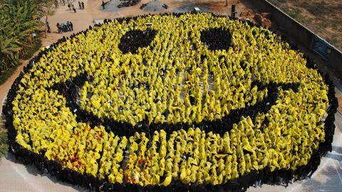 4444 students from 25 schools in Gwalior stand together and form a smiley face by holding coloured cloths in Gwalior on February 8, 2012 in an attempt to break the Guiness Book World Record of the largest human smiley face. AFP PHOTO/STR (Photo credit should read STRDEL/AFP/Getty Images)
