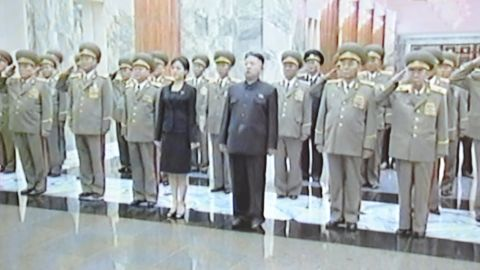 This screen grab taken from North Korean TV on July 9, 2012 shows an unidentified woman accompanying North Korean leader Kim Jong-Un (C) during his visit to Kumsusan Palace in Pyongyang on July 8, 2012 to pay tribute to his late grandfather Kim Il-Sung on the anniversary of his death in 1994. A mystery woman pictured accompanying North Korea's new leader Kim Jong-Un to recent events has prompted speculation in Seoul about whether she is his partner or his younger sister. ----