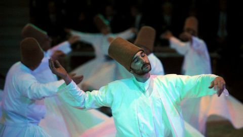 """A dervish whirls in religious ecstasy in the Turkish city of Konya, where the Sufi mystic Rumi is buried. """"Muslim for a Month"""" tours visit the tomb and observe the dervishes."""