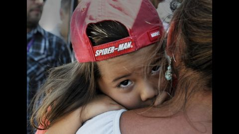Adariah Legarreta, 4, is comforted by her grandmother Rita Abeyta near the Century 16 Theater in Aurora.