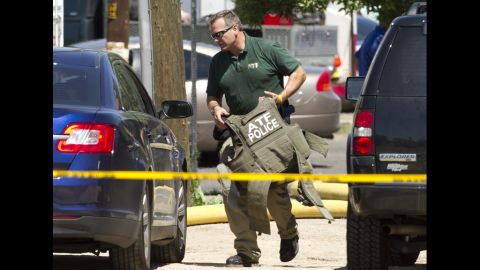 A Federal ATF officer carries protective gear onsite at the home of the shooting suspect.