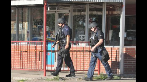 Members of the Aurora Police Department SWAT unit walk near the Holmes' apartment.