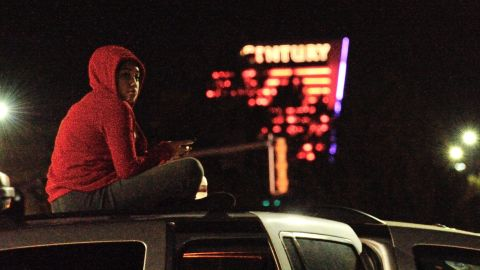 A woman sits on top of her car near the crime scene.