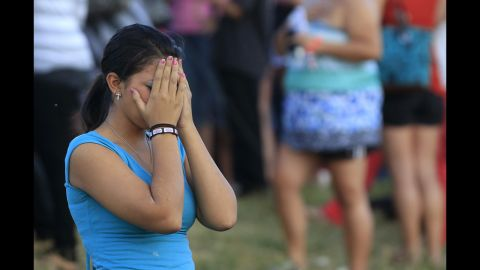 A woman grieves during a vigil for victims behind the theater.