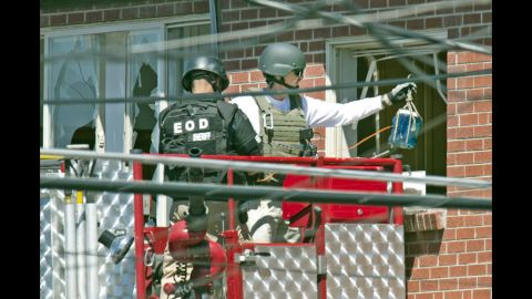 Officers prepare to place an explosive device inside the apartment.