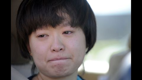 Lin Gan of Aurora holds back tears as she speaks to reporters about her experience in the Century 16 theater.