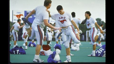 """The Southern Methodist University football team warms up in 1988, two years after a scandal broke that SMU boosters had been giving football players thousands of dollars from a slush fund with university officials' knowledge. In what was the first and last time it gave the """"death penalty"""" to a football program, the NCAA suspended SMU from playing its 1987 season and banned it from recruiting. The school also was not allowed to play at home in the 1988 season and lost dozens of scholarships."""