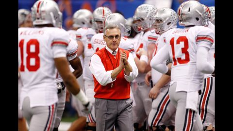 """Head coach Jim Tressel with his Ohio State Buckeyes at the 2011 Sugar Bowl. Tressel admitted he knew several star players were trading memorabilia for cash and tattoos in violation of NCAA rules. The NCAA banned the Buckeyes from postseason play for the upcoming season, and OSU voluntarily vacated all 2010 wins. Tressel """"resigned"""" in May 2011, a move OSU later deemed a retirement."""