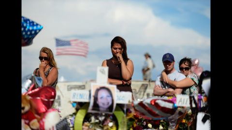 """Cynthia Davis, center, visits the roadside memorial set up for victims of the Colorado shooting massacre across the street from the Century 16 movie theater on Monday, July 30, 2012, in Aurora, Colorado. Twelve people were killed in the theater early July 20, 2012, during a screening of """"The Dark Knight Rises."""" Suspect James Holmes was taken into custody shortly after the attack. More photos: Colorado movie theater shooting"""