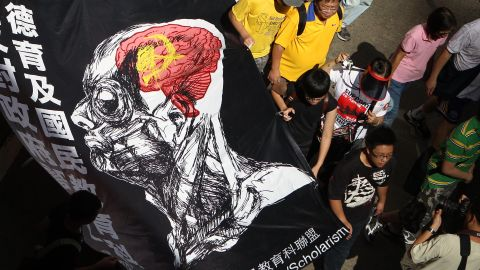"""Protester march against  implement national education in Hong Kong, claiming it amounts to Chinese patriotic """"brainwashing'."""