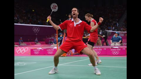 Joachim Fischer and Christinna Pedersen of Denmark celebrate beating Sudket Prapakamol and Saralee Thoungthongkam of Thailand in their mixed doubles badminton match.