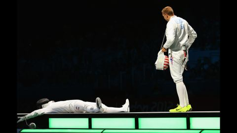 Jinsun Jung collapses after winning the men's epee individual fencing bronze medal match against Seth Kelsey of the United States.