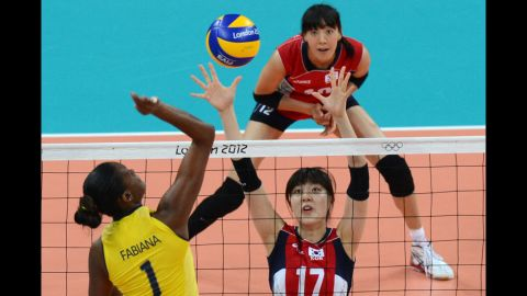 Brazil's Fabiana Claudino, left, spikes as South Korea's Yang Hyo-Jin, right, attempts to block during the women's preliminary group B volleyball match.