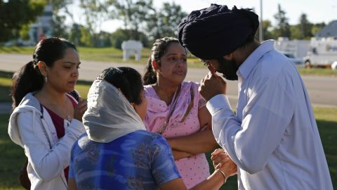 People console each other on Monday at the command center near the Sikh Temple of Wisconsin.