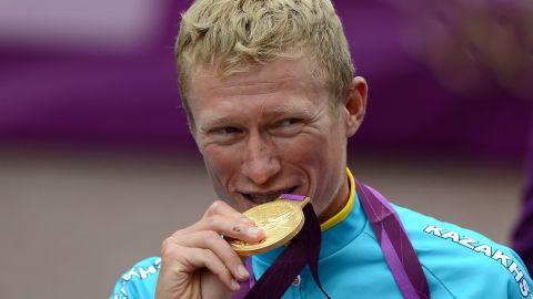 Alexander Vinokourov of Kazakhstan bites his gold medal after winning the men's road race cycling event.
