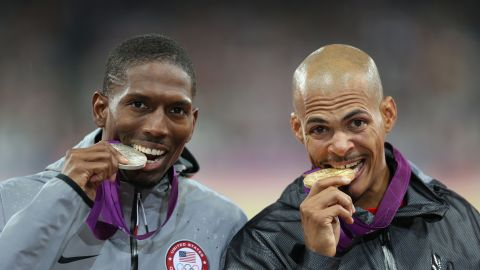 Silver medalist Michael Tinsley of the United States and gold medalist Felix Sanchez of Dominican Republic bite their medals after the men's 400-meter hurdles final.