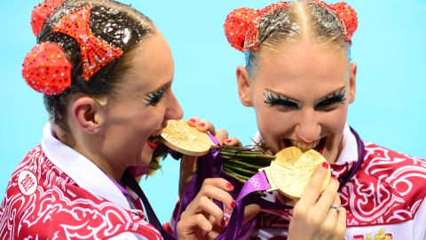 Russia's Natalia Ishchenko and Svetlana Romashina bite their medals after winning gold in the duets free routine final during the synchronized swimming competition at the London 2012 Olympic Games.
