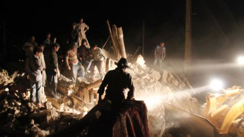 Aided by searchlights, residents and rescue workers search for survivors in the rubble of a village near Varzaqan on Saturday.