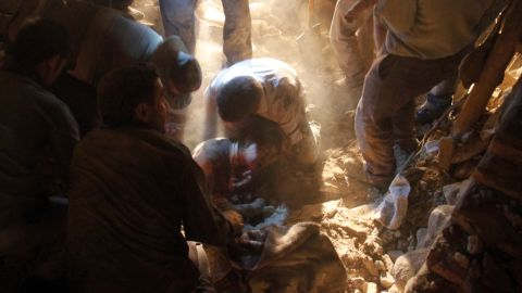 A woman is pulled from the rubble of a house in a village near  Varzaqan.
