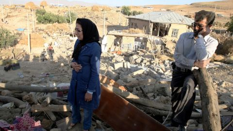 An Iranian man and woman stand on top of the rubble of their destroyed house in the village of Baje-Baj on Sunday.