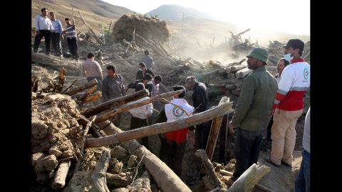 Iranian residents and rescue workers search for survivors in the rubble of a house in the village Baje-Baj.